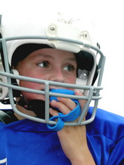 Child in football helmet with mouth guard - Pediatric and Cosmetic Dentists Keller, and Southlake TX - Donohue & Donohue, DDS